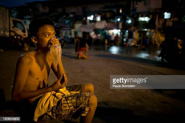 A young boy inhales glue mixed with nail polish remover in a plastic bag living in the slums of Binondo August 21 2012 in Manila Philippines He gets...