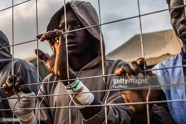 A young boy injured during a mass jump to the fence separating the Spanish city of Melilla from the Moroccan province of Nador clings to the fence...