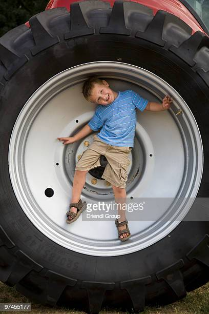 A young boy inside a large tractor wheel.