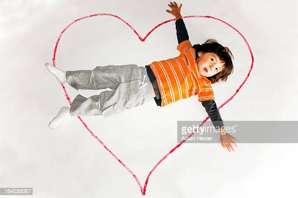 A young boy inside a red heart on white paper.