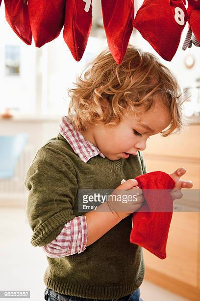 Young boy inspecting a christmas sack