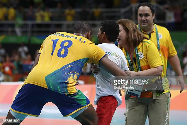A young boy invades the court to take pictures with brazilian players after the men's qualifying volleyball match between the Brazil and Canada on...