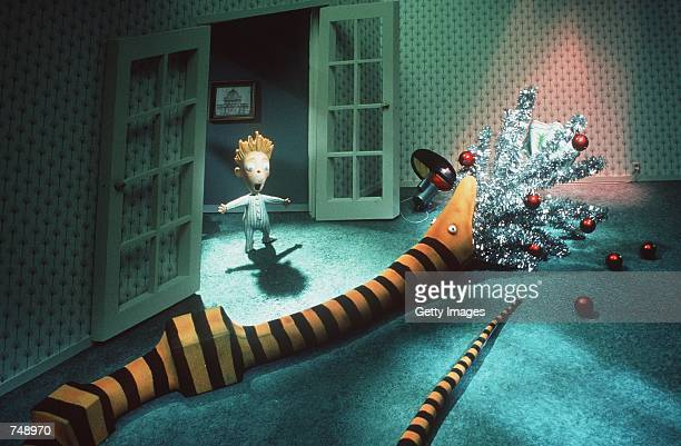 A young boy is astonished to see one of Santa's gifts an over sized snake devour the family Christmas tree in Touchstone Pictures animated film Tim...
