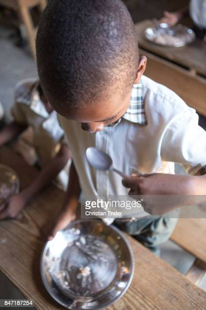 A young boy is eating rice his plate is almost empty