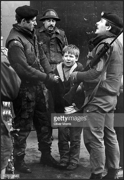 A young boy is held by British soldiers from the Gloucester Regiment after he was caught in the act of hurling stones at a Saracen Armoured Personal...