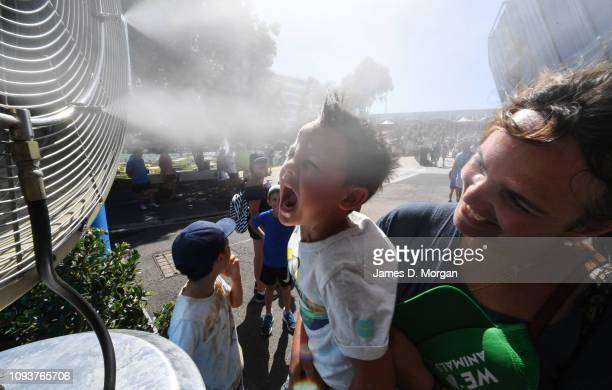 Young boy is held to a water fan during day one of the 2019 Australian Open at Melbourne Park on January 14, 2019 in Melbourne, Australia....