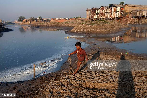 HAZARIBAGH DHAKA BANGLADESH A young boy is playing near the untreated chemical and leather waste in Hazaribagh Dhaka's Hazaribagh area widely known...