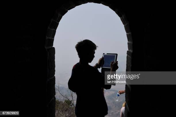 A young boy is seen taking picture with his iPad on a section of the Great Wall of China on April 5 2017 in Mutianyu China