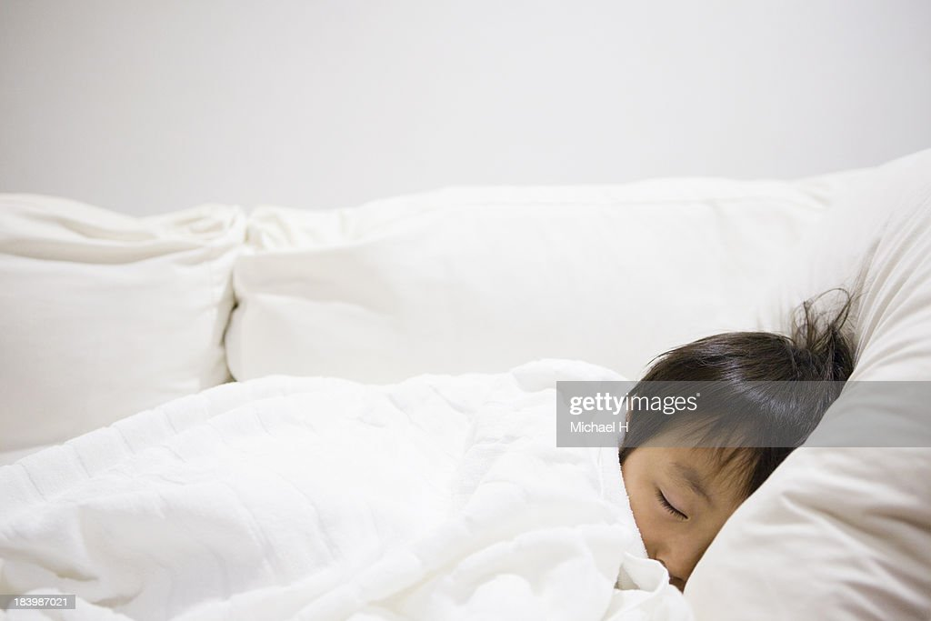 A young boy is sleeping in the bed : Stock Photo