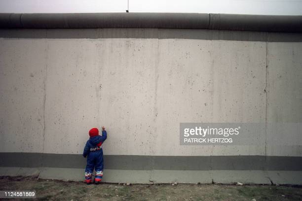A young boy is trying to show his talent by drawing on the East side of the Berlin Wall on November 21 a few yards from the newlyopened crossing at...