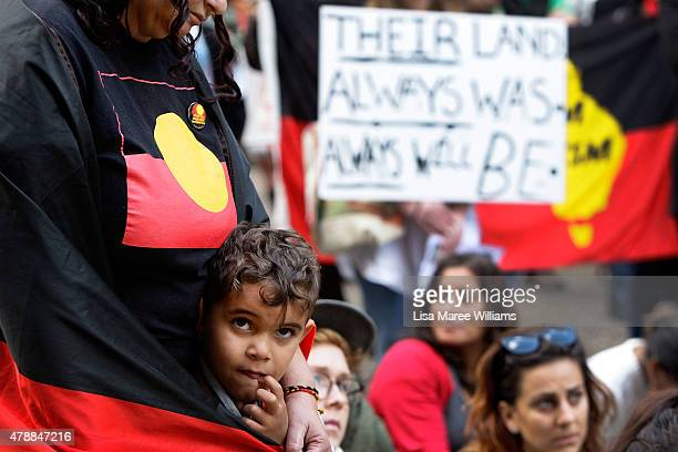 A young boy is wrapped in a Aboriginal flag at Sydney Town Hall on June 28 2015 in Sydney Australia A large number of protesters gathered in Sydney...