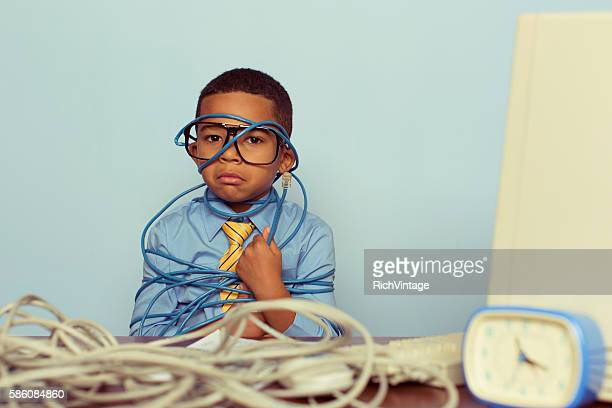 Young Boy IT Professional Frowns at Computer with Wire