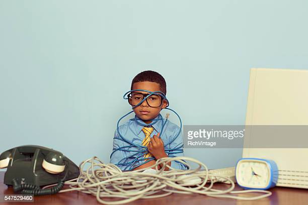 young boy it professional smiles at computer with wire - kabel stock-fotos und bilder