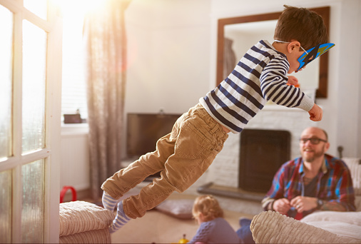 A young boy jumping from one sofa to another - gettyimageskorea