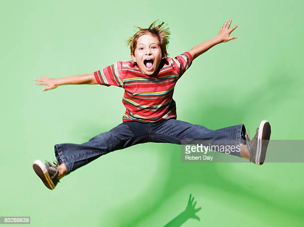 young boy jumping in mid-air - vreugde stockfoto's en -beelden