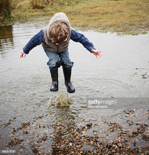 Young boy (3-5yrs) jumping in puddle