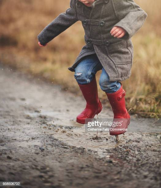young boy jumping in puddle - mud stock pictures, royalty-free photos & images