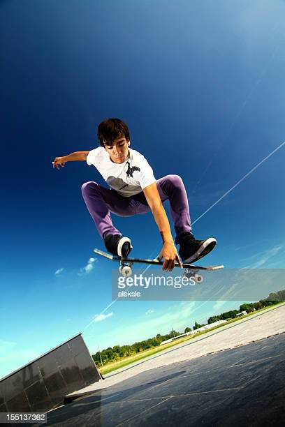 Young boy jumping in the air on a skateboard
