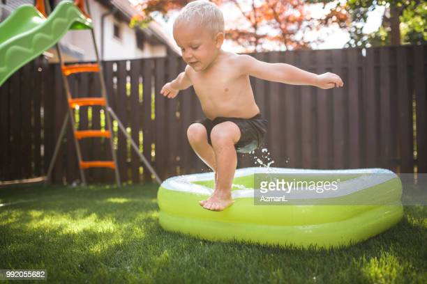 Young boy jumping into the inflatable pool
