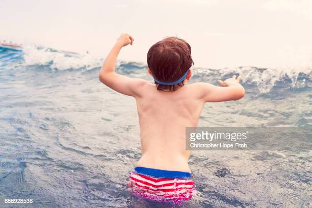 Young boy jumping into wave