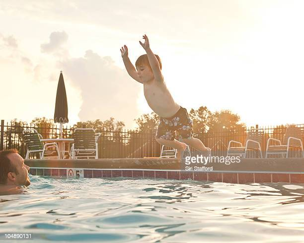 Young boy jumping off edge of pool