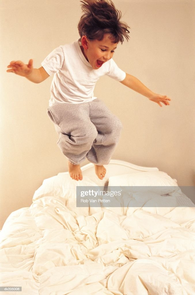 Young boy jumping on bed : Stock Photo
