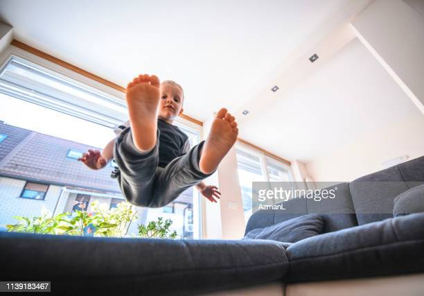 young boy jumping on sofa - women's field event stock pictures, royalty-free photos & images