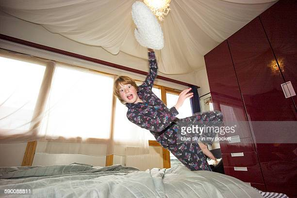 A young boy jumping on the bed