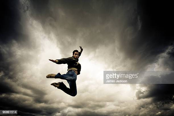 Young boy Jumping with dramatic clouds