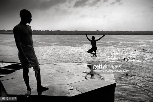 Young boy jumps in river ganges as his friend looks on during a monsoon morning in benaras.