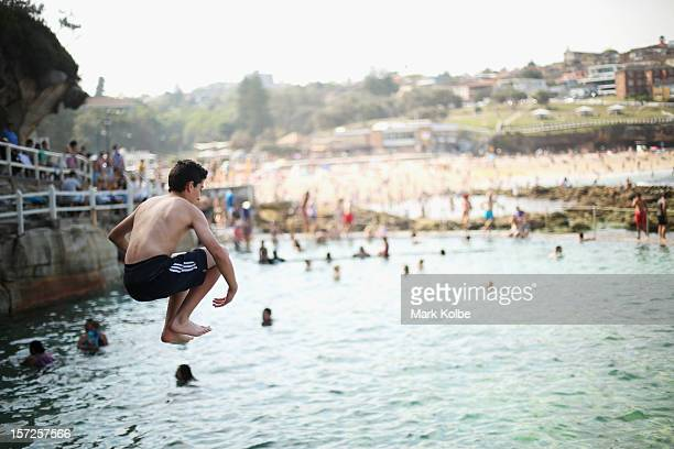 A young boy jumps into the beachside Bronte pool at Bronte beach on December 1 2012 in Sydney Australia Temperatures in the high 30s have seen people...