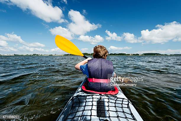 Young Boy Kayaking at Sea with Oar Paddling in Water