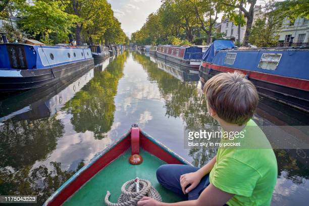 a young boy keeping watch on the bow of a narrow boat - はしけ ストックフォトと画像