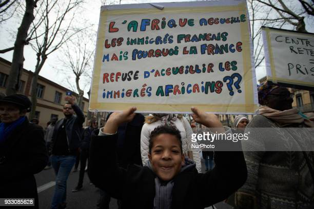 A young boy keeps a placard reading 'Africa welcomes French emigrants but why France doesn't want to welcome Africans emigrants' More than 1000...