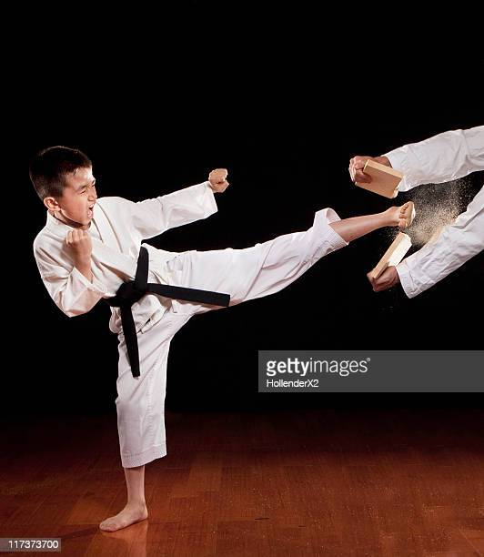 young boy kicking and breaking wood - aggression stock pictures, royalty-free photos & images