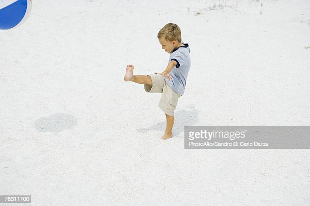 Young boy kicking beach ball at the beach, side view