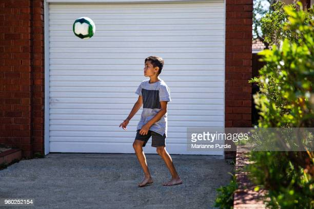 Young boy kicking football on driveway