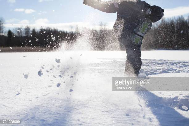 Young boy kicking snow, in snow covered landscape, low section
