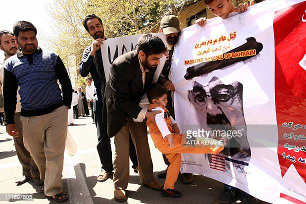 A young boy kicks a portrait of Saudi King Abdullah during a demonstrate next to the Saudi Arabia embassy in Tehran on April 8 to support Bahrain...