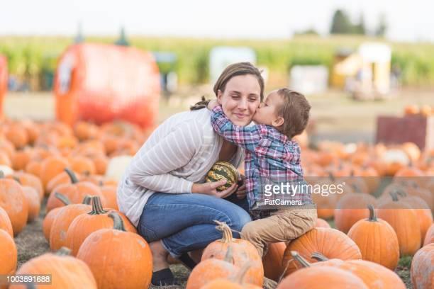 Young boy kisses his mom at a pumpkin farm