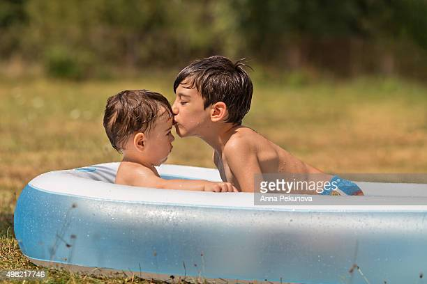 Young boy kissing his toddler brother