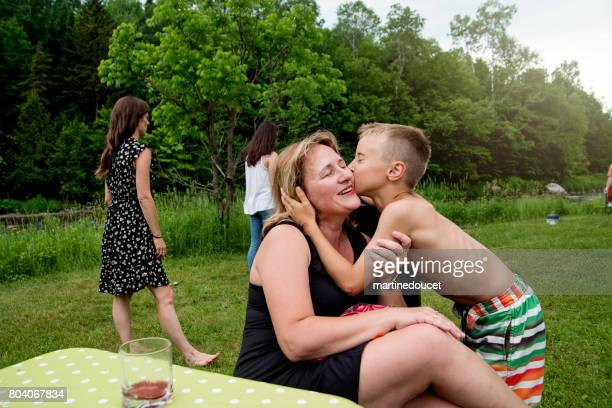 Young boy kissing mother at family reunion outdoors.