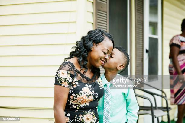 Young boy kissing mother on cheek on front porch of home