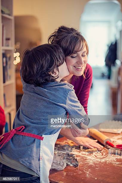Young boy kissing mother while making gingerbread cookie at home.
