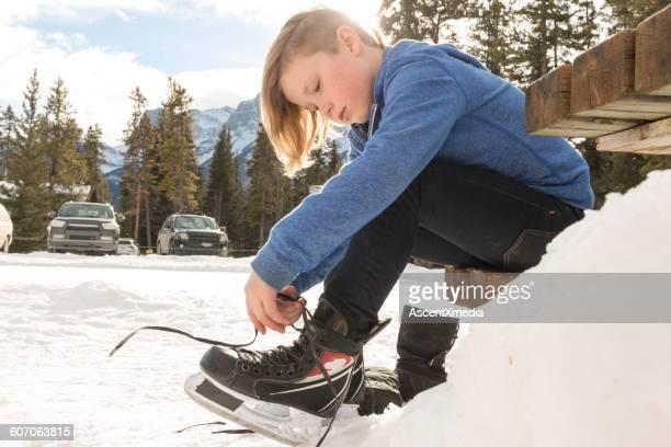 Young boy laces up skates, at edge of skating pond