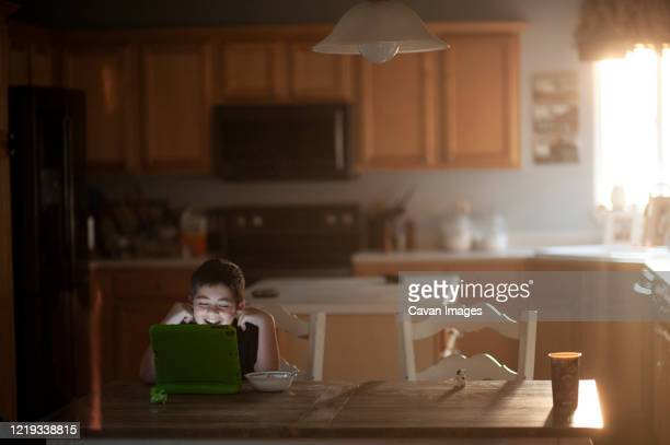 young boy laughing while watching tablet at kitchen table eating food - autism stock pictures, royalty-free photos & images