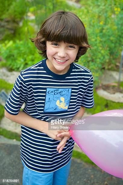Young Boy Laughing with Pink Balloon