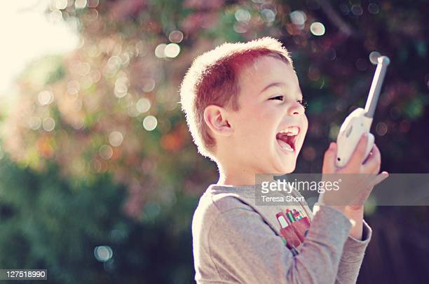 Young boy laughing with walkie alkie