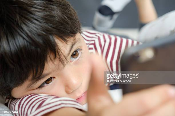 Young boy laying down looking at a smartphone
