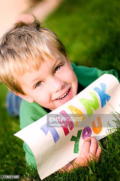 Young boy laying in grass holding thank you sign